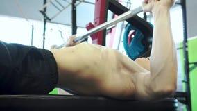 Hombros jovenes del tren de Powerlifter del varón y músculos del pecho que hacen la prensa de banco almacen de metraje de vídeo