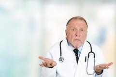 Hombros profesionales del encogimiento de hombros del doctor de la atención sanitaria mayor desorientada Fotos de archivo libres de regalías