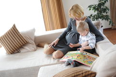 At home. Pregnant mother and her son reading a book Stock Photos
