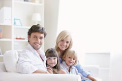 Home. Young family with two children on a white sofa at home Royalty Free Stock Photo