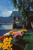 Home. Ahouse in the background is shadowed by a lovely garden full of colorful flowers Stock Photos