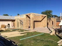 Home Addition Framing Building Erection. Home addition wood adding on house erection building walls lumber timber grass construction planning phase business stock photos