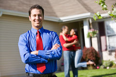 Home: Agent with Excited Couple in Background. Extensive series of a Caucasian Real Estate Agent and African-American Couple in front of a home Royalty Free Stock Images