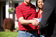 Home: Agent Meeting with Homebuyers. Extensive series of a Caucasian Real Estate Agent and African-American Couple in front of a home Stock Photos