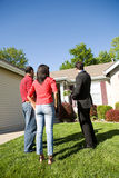 Home: Agent Shows Home to Couple. Extensive series of a Caucasian Real Estate Agent and African-American Couple in front of a home Royalty Free Stock Images