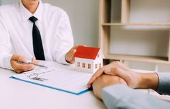 Home agents are sending pens to customers signing a contract to buy a new home.  stock photography