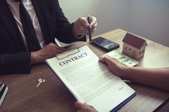 Home agents talking to home buyers who are signing contracts at the office.  stock images