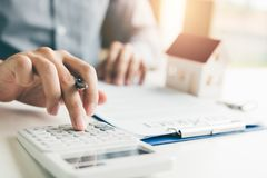 Home agents are using a calculator to calculate the loan period. Each month for the customer royalty free stock photography