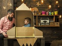 Home airfield. Boy play with dad, father, little cosmonaut sit in rocket made out of cardboard box. Kid happy sit in. Cardboard hand made rocket royalty free stock photography