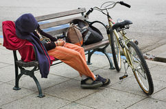 Home Alone. A homeless person trying to sleep on a bench royalty free stock images