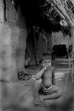 Home Alone. An Indian village boy is sitting in front of his house Royalty Free Stock Photography