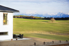 Home and Alps mountains. Exterior of luxurious modern house with green fields and snow capped Alps mountains in background, Germany Royalty Free Stock Images
