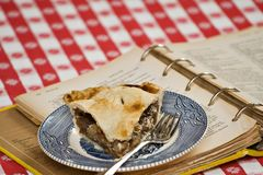 Home Apple Pie. A piece of homemade apple pie - vintage plate and actual recipe book used to make the pie Royalty Free Stock Photo