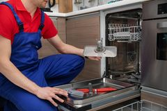 Free Home Appliance Maintenance - Handyman Removing Dirty Dishwasher Food Residue Filter Stock Photography - 140772782