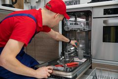 Home appliance maintenance - repairman repairing dishwasher in kitchen royalty free stock photography