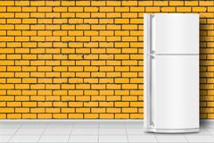 Home appliance - Refrigerator in front of yellow brick wall. Major appliance - Refrigerator in front on a yellow brick wall background stock image