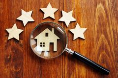 Home appraisal. House with magnifying glass and five star stock photo