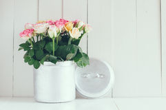 Home arrangement. Vintage home arrangement, bright summer roses in aluminium jar on a barn wall background Stock Image