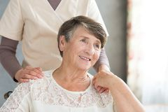Assistant supporting smiling old lady. Home assistant in uniform supporting smiling old lady during visit stock images