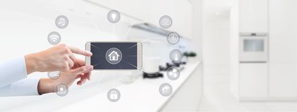 Home automation hand touch smart phone screen with symbols on ki. Tchen blurred background Royalty Free Stock Images