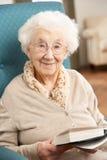 home avslappnande hög kvinna för stol Arkivbild