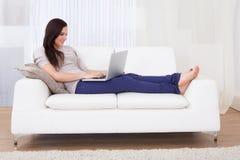 home bärbar dator genom att använda kvinnan Arkivbild