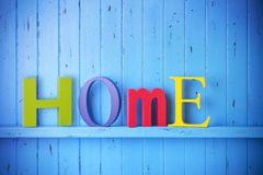 Home Background. A blue painted background with the word home spelled out in colourful letters Stock Image