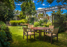 Home backyard garden. Home backyard with modern garden table set in sunny a lush garden with shade of trees stock photos