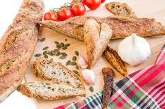 Home baked baguettes, fresh and dry tomatoes, garlic, pumpkin se Stock Photography