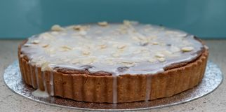 Home baked Bakewell Tart cake on foil platter. Photo shows pastry, white icing and flaked almonds. Home baked Bakewell Tart cake on silver foil platter. Photo stock photos