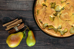 Home baked biscuit flavored pear charlotte cake with cinnamon. On a dark wooden background. Stock Photo