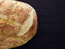 Home baked bread. Loaf of home baked bread on dark brown wooden surface shot from above Stock Image