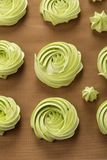 Home baked green meringues cookies. Top view. Closeup home baked green meringues cookies rosette shape on silicone mat. Homemade meringues kisses. Top view stock photo