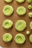 Home baked green meringues cookies. Top view. Closeup home baked green meringues cookies rosette shape on silicone mat. Homemade meringues kisses. Top view royalty free stock images