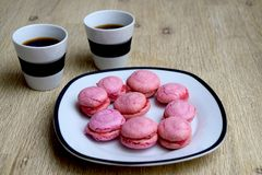 Cup of coffee and pink french macarons royalty free stock photography