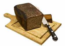 Home Baked Rye Bread. A home baked loaf of Rye bread, with one slice cut from the end and lying beside it. All standing on a breadboard with a breadsaw. The Royalty Free Stock Photography
