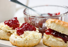 Home baked scones with strawberry jam and clotted. Home-baked scones tea with strawberry jam and clotted cream. Shallow depth of field Royalty Free Stock Photography