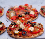 Home baked vegan mini pizza on parchment paper. Home baked vegan mini pizza with olives, red pepper, tomato, pear, oregano and pesto on parchment paper Royalty Free Stock Images