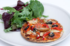 Home baked vegan mini pizza with ruccola salad Royalty Free Stock Image