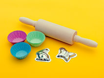 Home baking cooking equipment - rolling pin etc. Wooden rolling pin, paper cake cases for cupcakes etc and chocolate or marzipan moulds over yellow - includes Royalty Free Stock Photos