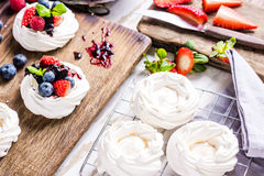 Home baking, Pavlova with fresh summer fruits. Home baking, Pavlova with fresh summer fruits, on wooden table in kitchen Stock Image
