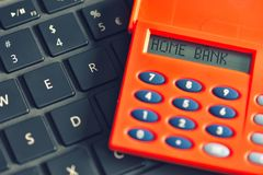 Home bank written on the display of the digipass over computer keyboard. Online banking transaction concept.  royalty free stock photos