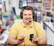 Home based computer tutor business. Middle-aged man has started home based computer tutor business. Experienced tutor in headset explains how to install audio Stock Images