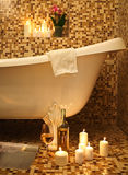Home bathroom interior with bubble bath. Candles, magazine and white whine. Relax concept Royalty Free Stock Photo