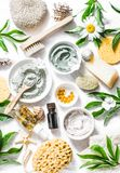 Home beauty products - clay, oatmeal, coconut oil, turmeric, lemon, scrub, dry flowers and herbs, sponges, soap, facial brush on l stock photos