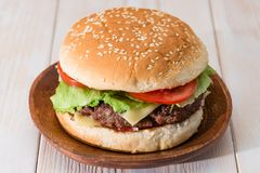 Classic burger close-up. Home big classic burger on a wooden table close-up royalty free stock image