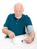 Home Blood Pressure Check. Senior man checking his blood pressure at home.  Isolated on white Stock Image