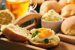 Home breakfast - homemade bread rolls, cup of tea, boiled eggs and garlic herb butter. Royalty Free Stock Images