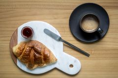 Home brew black coffee with creama served with delicious buttery croissant and strawberry jam on white marble plate stock photos