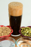 Home brew ingredients of grain, hops, yeast and water. Home brewed beer with head foaming over behind the four beer ingredients of malted barley grain, hop Stock Image